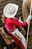High angle view of a woman wearing a white cowboy hat and riding a horse at the Calgary Stampede; Calgary, Alberta, Canada