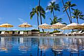 Halekalani Pool at Waikiki with palm trees and umbrellas reflected in the water; Waikiki, Oahu, Hawaii, United States of America