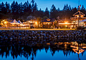 The heritage site tourist attraction Union Steamship Building in Snug Cove, Bowen Island is lit up at night welcoming tourists to the restaurant, shops and marina a quick ferry ride from Vancouver, BC; Bowen Island, British Columbia, Canada