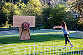 A woman throws an axe at a target at a recreational axe throwing game during a logging festival; Bowen Island, British Columbia, Canada
