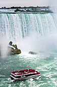 Close-up of Niagara Falls with tourist boat going towards the falls; Niagara Falls, Ontario, Canada