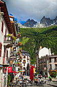 Massive peaks of Aiguilles Rouges over the outdoor cafe and hotels in the Chamonix city centre; Chamonix-Mont-Blanc, Haute-Savoie, France