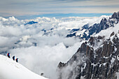 Mountain climbers departing Aiguille du midi, surrounded by French Alps summits; Chamonix-Mont-Blanc, Haute-Savoie, France