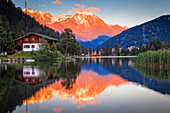 Pastel-coloured sunset glow on the mountains reflecting on Champex Lake; Champex, Valais, Switzerland