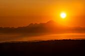Glowing Sun During A Golden And Orange Sunset Over Kenai Mountains, Kachemak Bay State Park; Alaska, United States Of America