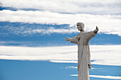 Statue Of Christ Against Blue Sky With Stripes Of White Clouds; Tupungato, Mendoza, Argentina
