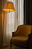 A Floor Lamp Illuminated Beside A Chair And Window; Cannes, Cote D'azur, France