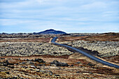 A Highway Runs Across A Barren Landscape With A Mountain In The Distance, Snaefellsnes Peninsula; Iceland