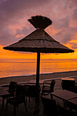 A Thatch Umbrella Over A Table With Chairs On The Beach At Sunset, Looking Out Over The Mediterranean Sea; Menton, Cote D'azur, France