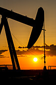 Silhouette Of A Pumpjack At Sunrise With A Colourful Orange Sun, Clouds And Sky; Alberta, Canada