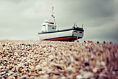 A fishing boat sits on the rocky beach under a cloudy sky; Hastings, England