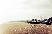A traditional fishing boat on the shore with mist along the coast; England