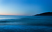 Seascape at sunset with clear, blue sky and tranquil ocean water, Karamea beach; South Island, New Zealand