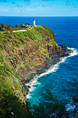 A lighthouse and trail along a ridge with steep cliffs on the coastline of the Island of Hawaii; Kilauea, Island of Hawaii, Hawaii, United States of America