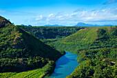 Landscape with dense, lush foliage and the tranquil, blue waters of the Wailua River; Wailua, Kauai, Hawaii, United States of America