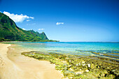 Clear turquoise ocean water and the rugged mountainous landscape on the island of Kauai; Kapaa, Kauai, Hawaii, United States of America