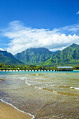 A pier leading out to the ocean water along the coastline with water washing onto the beach in the foreground and rugged, green mountains in the background; Hanalei, Kauai, Hawaii, United States of America