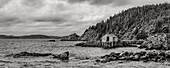 Black and white image of the rocky Atlantic coastline with a dock and boat house; Newfoundland, Canada