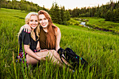 Two girlfriends sitting in a grass field in an embrace posing for a portrait at sunset; Edmonton, Alberta, Canada