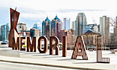 A sign spelled in lettering for Memorial Drive with the Calgary skyline in the background; Calgary, Alberta, Canada