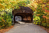 A covered bridge on a back country road in autumn, White Mountains National Forest; New England, United States of America