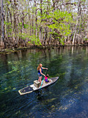 A mother and daughter paddleboard down the stream of freshwater spring; Chiefland, Florida, United States of America