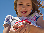 A young girl shows off a ladybug (Coccinellidae) she caught and is holding on her thumb; Destin, Florida, United States of America