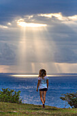Back view of woman looking to sea by sunset, Nusa Penida island, Bali, Indonesia