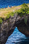 Family walking across coastal arch, Nusa Penida island, Bali, Indonesia