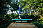 Woman doing yoga on wooden platform, Wellawaya, Uva Province, Sri Lanka