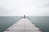 Person standing at end of pier in sea under overcast sky, Malmo, Skane County, Sweden