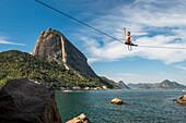 Man posing on high line in Contos De Pescadores, Vermelha Beach, Rio de Janeiro, Brazil