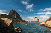 Woman doing aerial acrobatics hanging from highline next to Sugar Loaf Mountain in Rio de Janeiro, Brazil