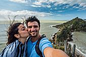 Woman kissing man on cheek while taking selfie in Buzios, Rio de Janeiro, Brazil