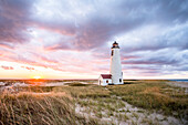 A vibrant colorful sunset of Nantucket's iconic Great Point Lighthouse, isolated on a stretch of sand 7 miles long in the Atlantic Ocean