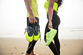 Man and woman standing on coastal beach and holding shoes, Hampton, New Hampshire, USA