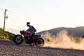 Side view of man riding motorcycle leaving dust cloud behind, Emigration Canyon, Utah, USA