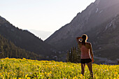 Female trail runner standing while resting in meadow, Alta, Utah, USA