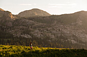 Female trail running near Alta Ski Resort with Devils Castle in the background