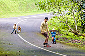 Father on skateboard accompanying sons on bicycles
