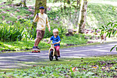 Father on skateboard with phone accompanying son on bicycle
