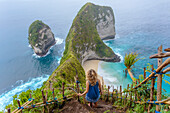 Blonde woman standing on cliffside steps admiring ocean coastline of Nusa Penida island, Bali, Indonesia