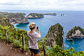 Woman standing on cliff photographing ocean coastline of Nusa Penida island, Bali, Indonesia