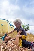 Father and son playing outside tent in meadow, Nusa Penida, Bali, Indonesia