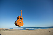An ukulele floats in the air above a remote beach scene in Baja California, Mexico.