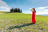 San Quirico d'Orcia, Orcia valley, Siena, Tuscany, Italy, A young woman in red dress admiring the view in a wheat field near the cypresses of Orcia valley