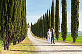 Castiglione d'Orcia, Orcia valley, Siena, Tuscany, Italy, A couple walking along a country road