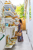Ravello, Amalfi coast, Salerno, Campania, Italy. A tourist is having a look at a pottery store in Ravello (MR)
