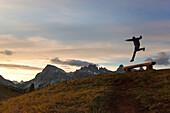 A hiker jumps in fornt of Lagazuoi, Dolomites, Cortina d'Ampezzo, Belluno province, Veneto, Italy