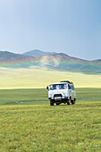 Rainbow and Soviet vehicle driving in the Mongolian steppe, Ovorkhangai province, Mongolia